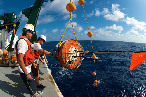 研究er out on the ocean on a large vessel hauling up a buoy to collect data.